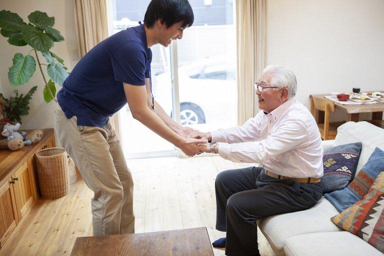 40代男性が介護士として介助している様子