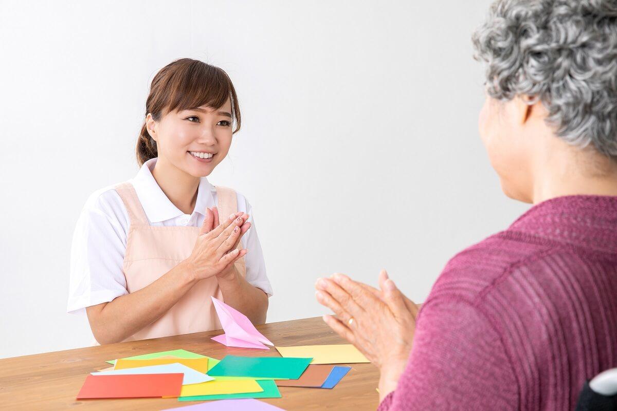 グループホーム・デイサービス併設施設で介護士が利用者と触れ合っている様子