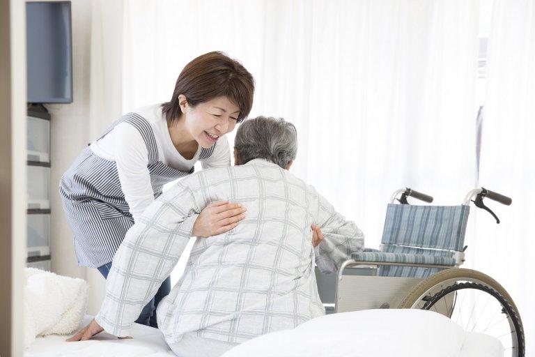 60歳の介護士が特別養護老人ホームで介助している様子